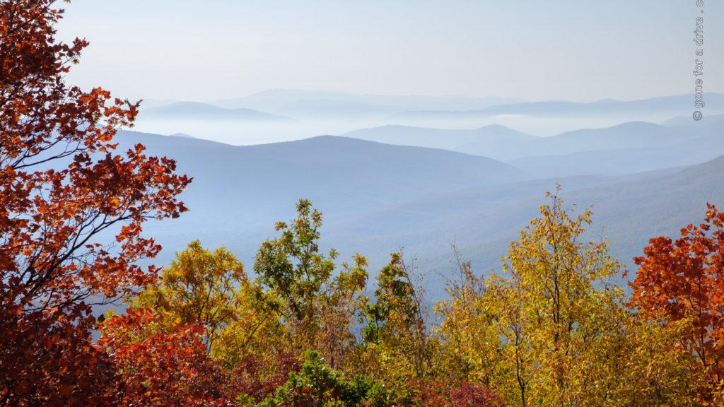 Blick über dunstverhangene Berge mit herbstlich gefärbten Laubbäumen im Vordergrund.