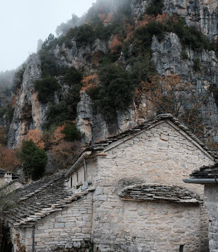 Steinhäuser vor Felshang im Nebel. Vikos-Schlucht, Griechenland..