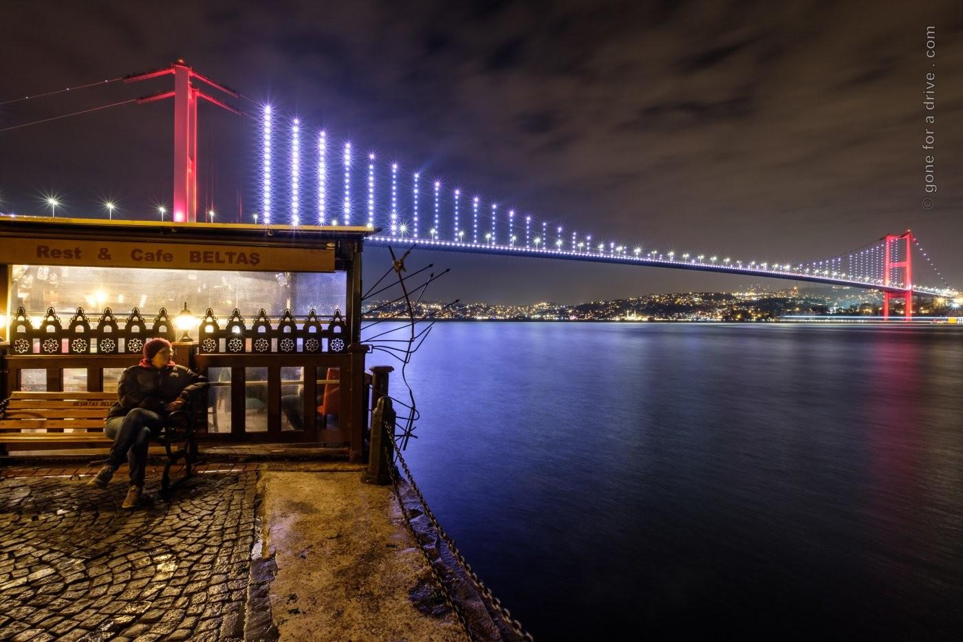 Blick auf die erste Bosporusbrücke in Istanbul, Türkei, bei Nacht mit beleuchtetem Café im Vordergrund.