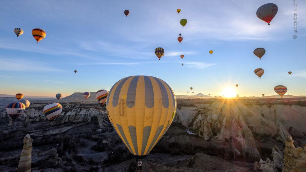 Heißluftballons in Kappadokien im Gegenlicht der aufgehenden Sonne