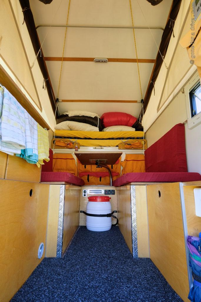 Ortec Minicamp Wohnkabine Innenausbau. Blick von der Eingangstür auf Spülblock, Unterschränke und Sitzbänke.