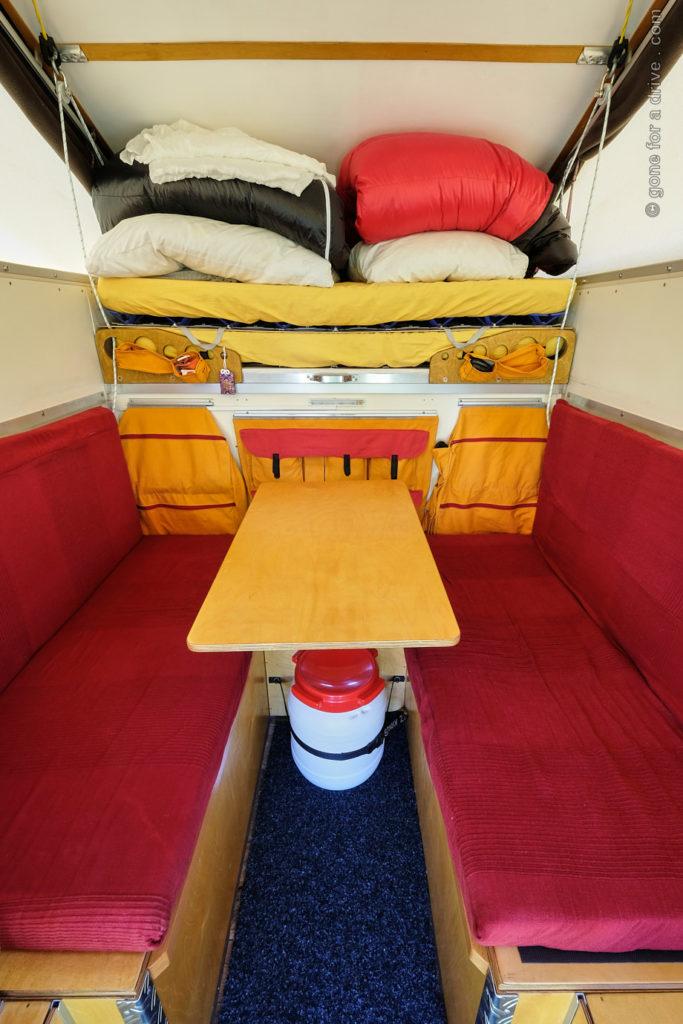 Ortec Minicamp Wohnkabine Innenausbau. Blick von der Eingangstür auf Sitzbänke, Tisch und Bett im Alkoven.